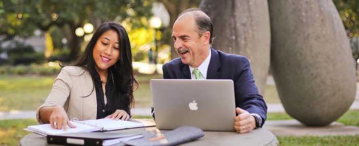 A professor and a student sitting outside and discussing continuing studies in New Orleans, LA
