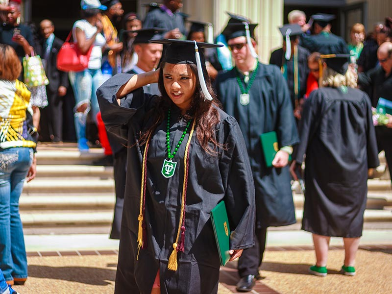 Student holding degree from Tulane School of Professional Advancement after commencement in New Orleans, LA