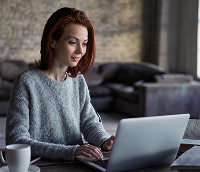 A redhead woman on a laptop representing the professional advancement programs at the Tulane School of Professional Advancement in New Orleans, LA