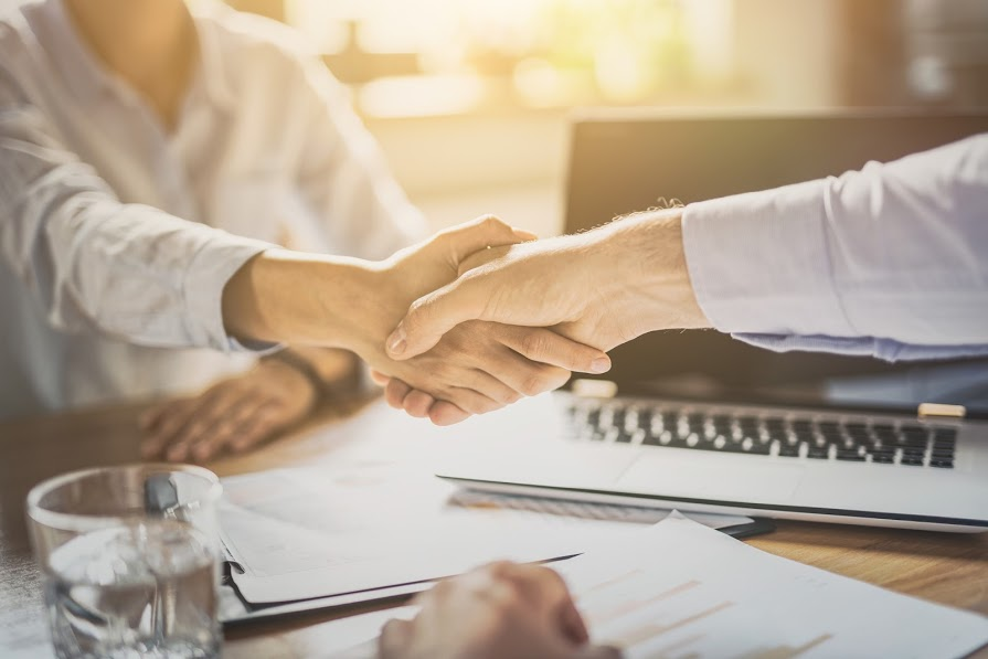 Two business people shaking hands over a desk
