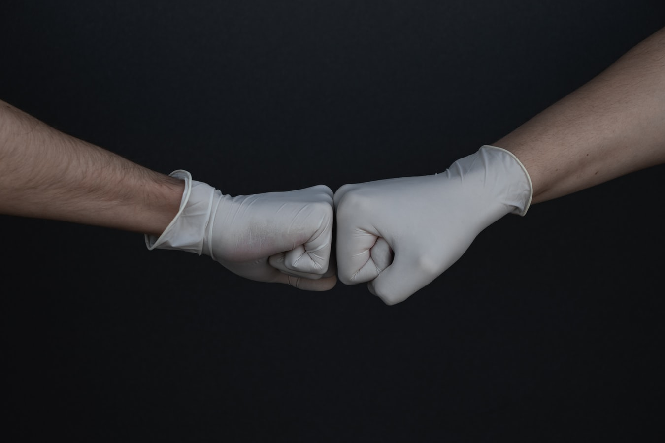 Two fists bumping while wearing medical gloves