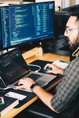 Man coding on laptop - Tulane School of Professional Advancement