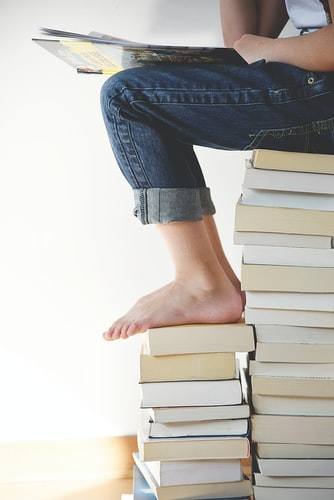 A person sitting an a stack of books