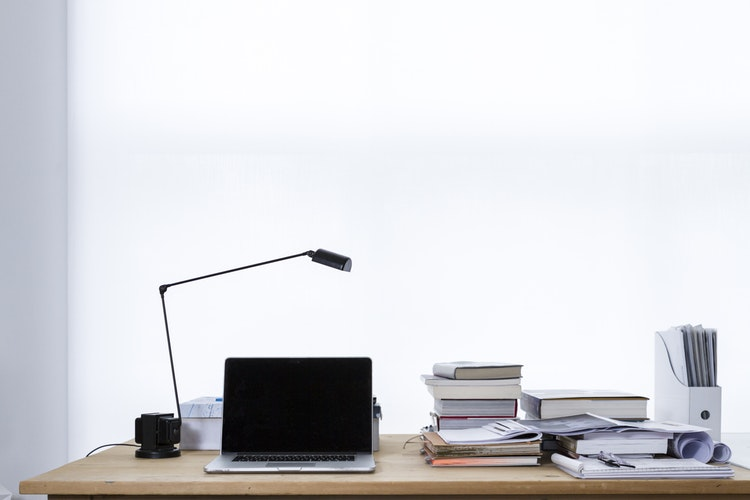 A desk with a laptop and books