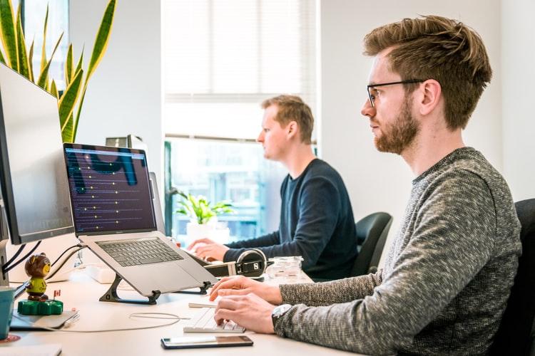 Two men working on desktop computers