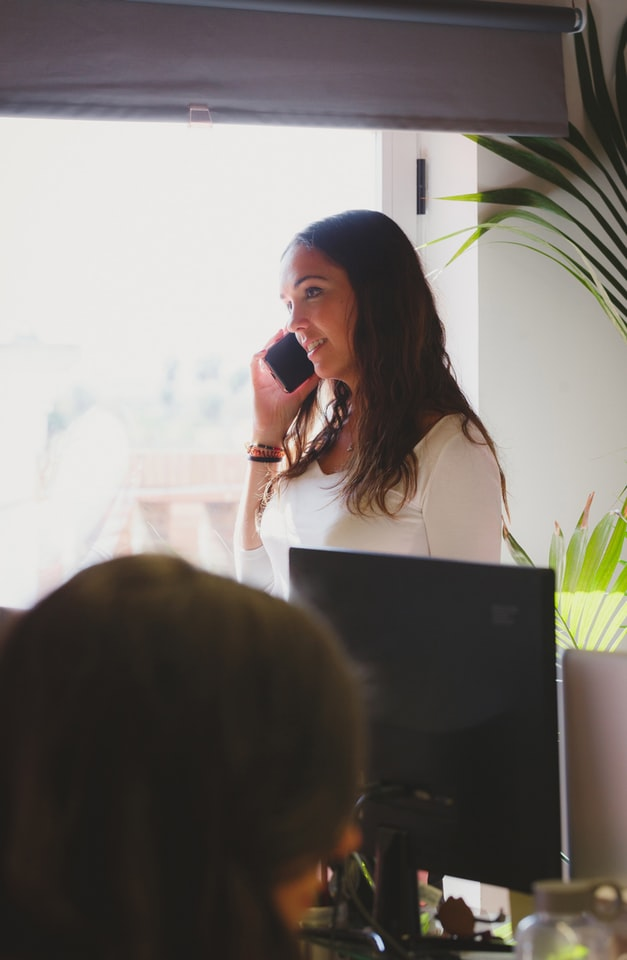 A woman talking on her phone in an office