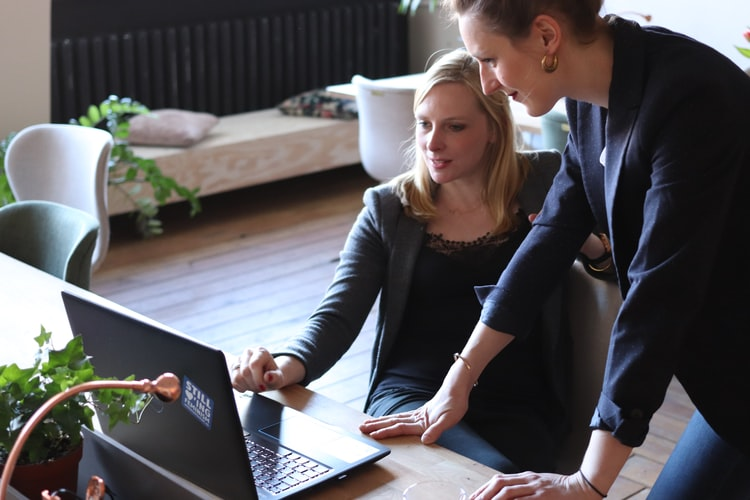 Two women professionals working on a laptop