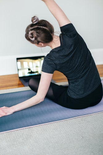 A person doing yoga while watching an instructional video
