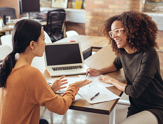 A woman talking to her professor about an accounting degree from Tulane School of Professional Advancement in New Orleans, LA