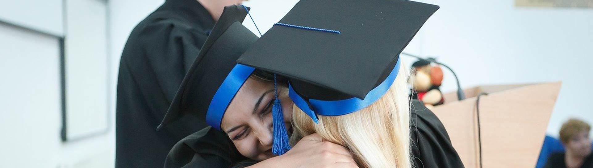 College graduates hugging on graduation day