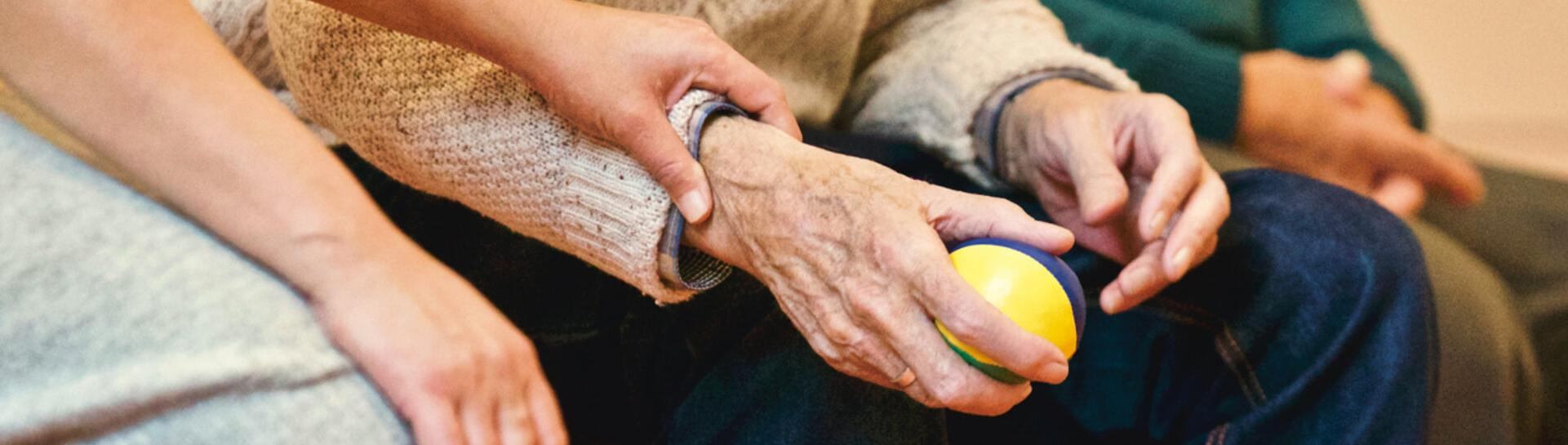 An elderly person squeezing a strength-building ball in their hand
