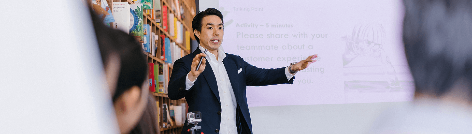 A man in a suit giving a lecture