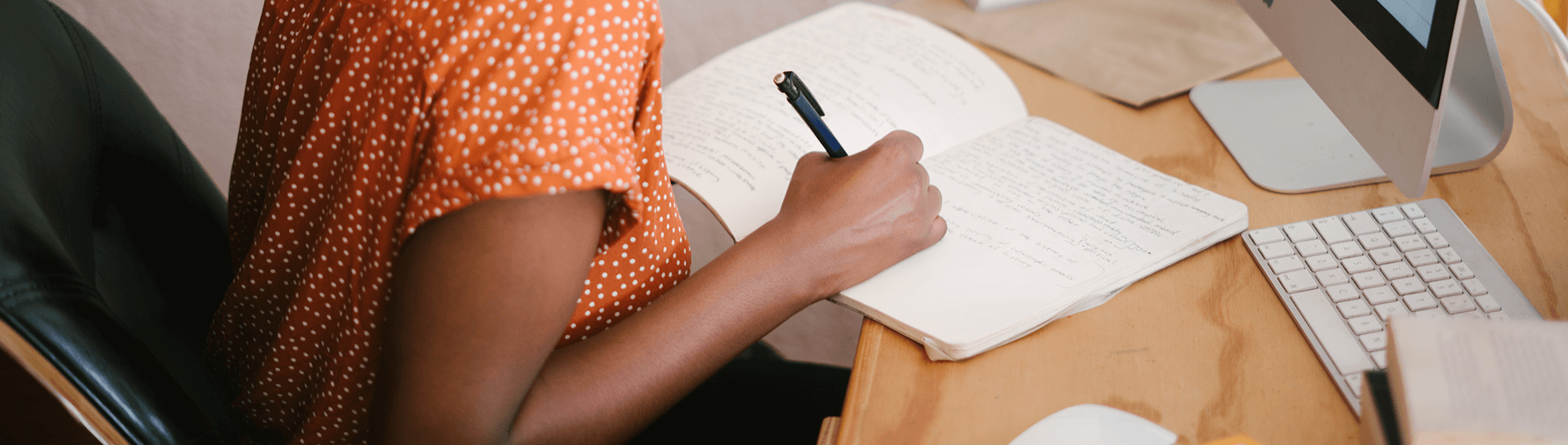 A student taking notes at their desk