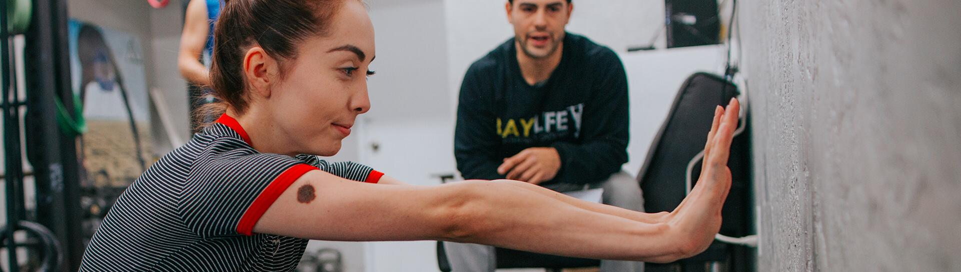 A person doing exercises with a trainer