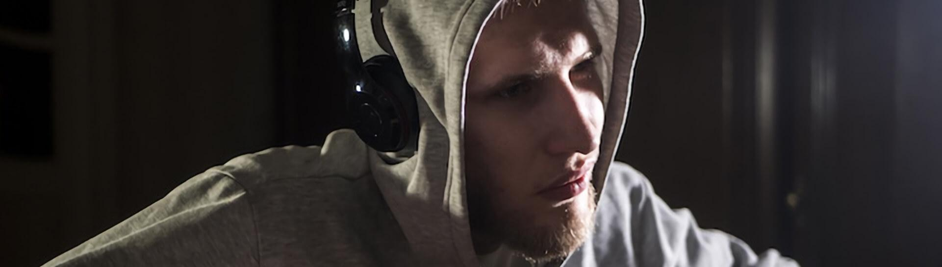 A man in a hoodie wearing headphones