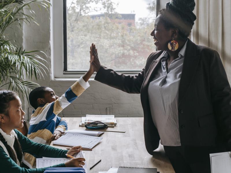 A teacher giving students a high five