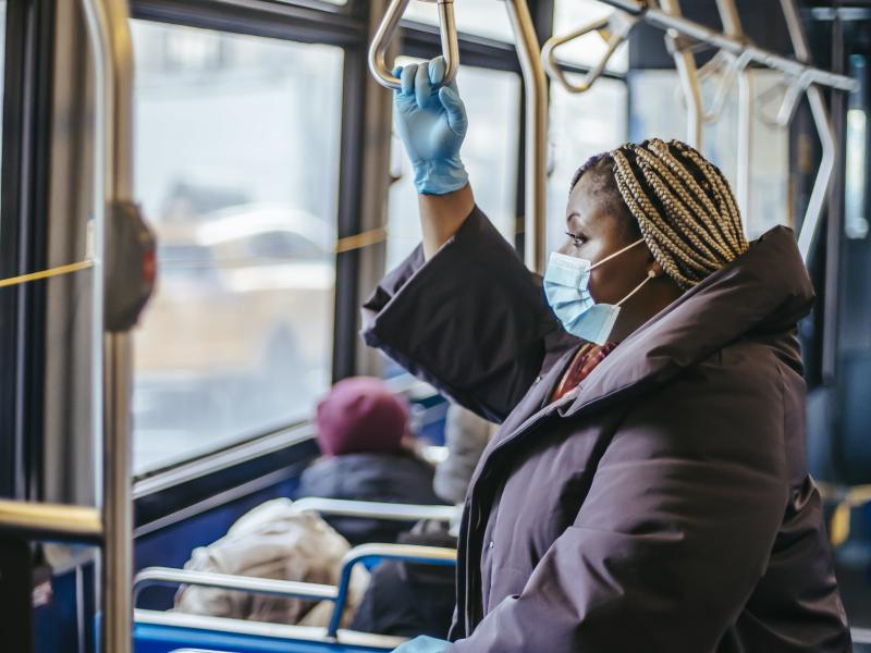 A woman wearing a mask and gloves on a bus