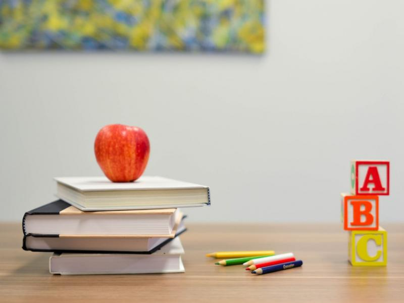 An apple and teaching supplies on a table