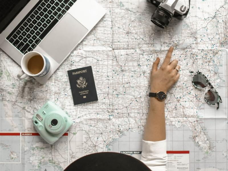 A person looking at a map with other travel accessories