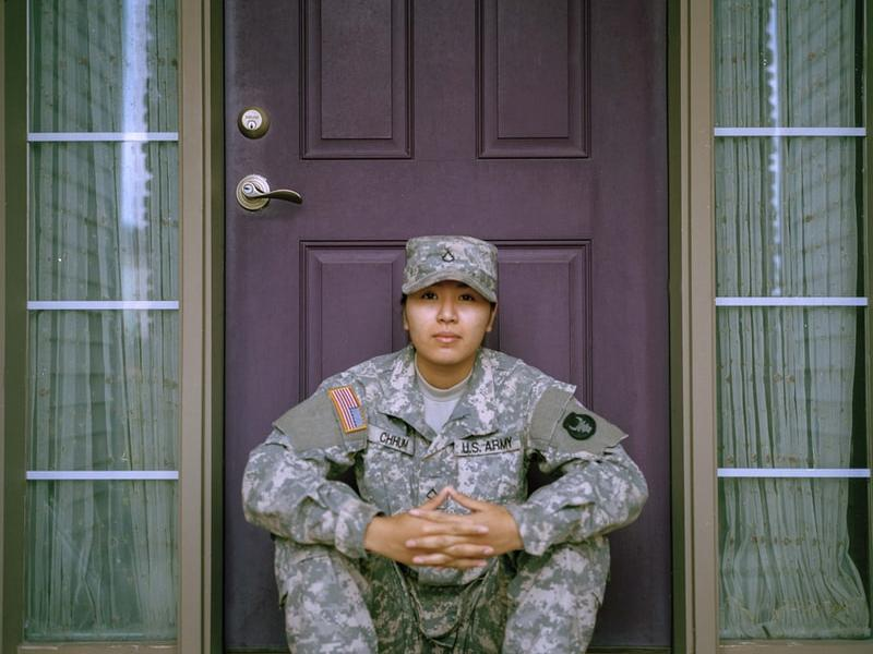 A woman in army cammies sitting in front of a door