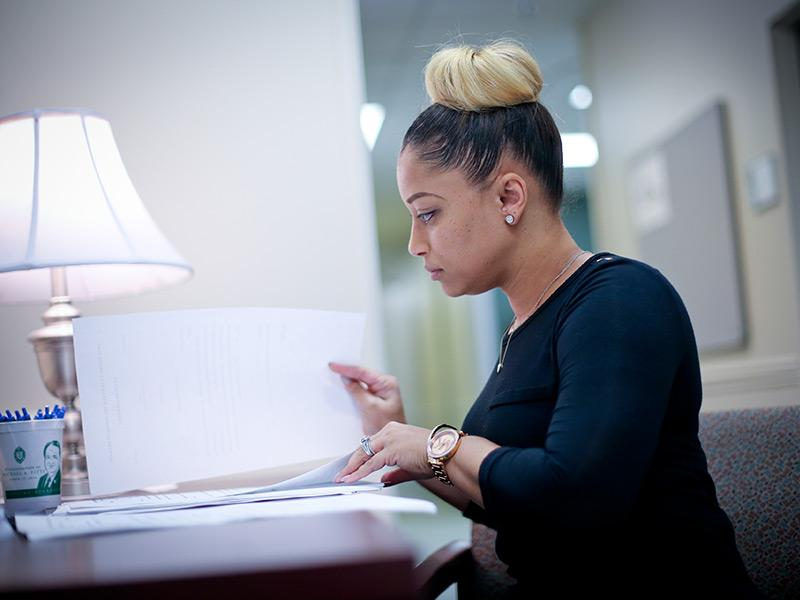 A woman at a desk going over paperwork